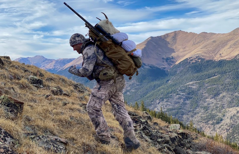 hunter packing out mountain goat