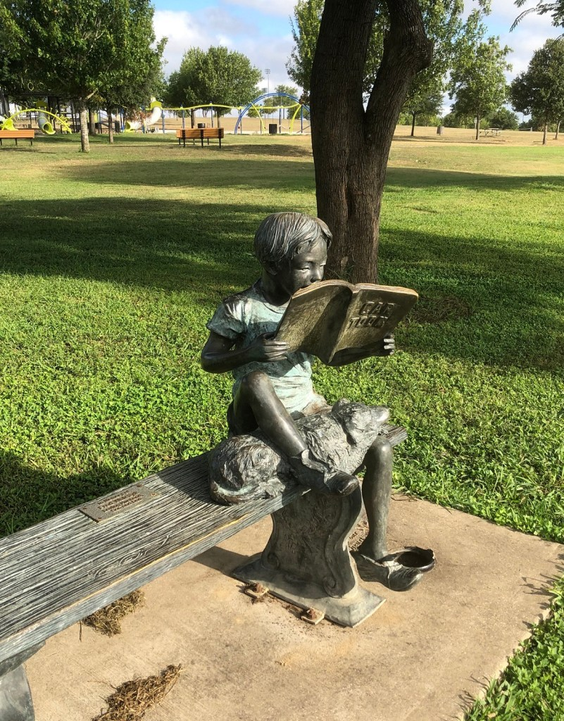 Statue of child reading in Old Settlers Park