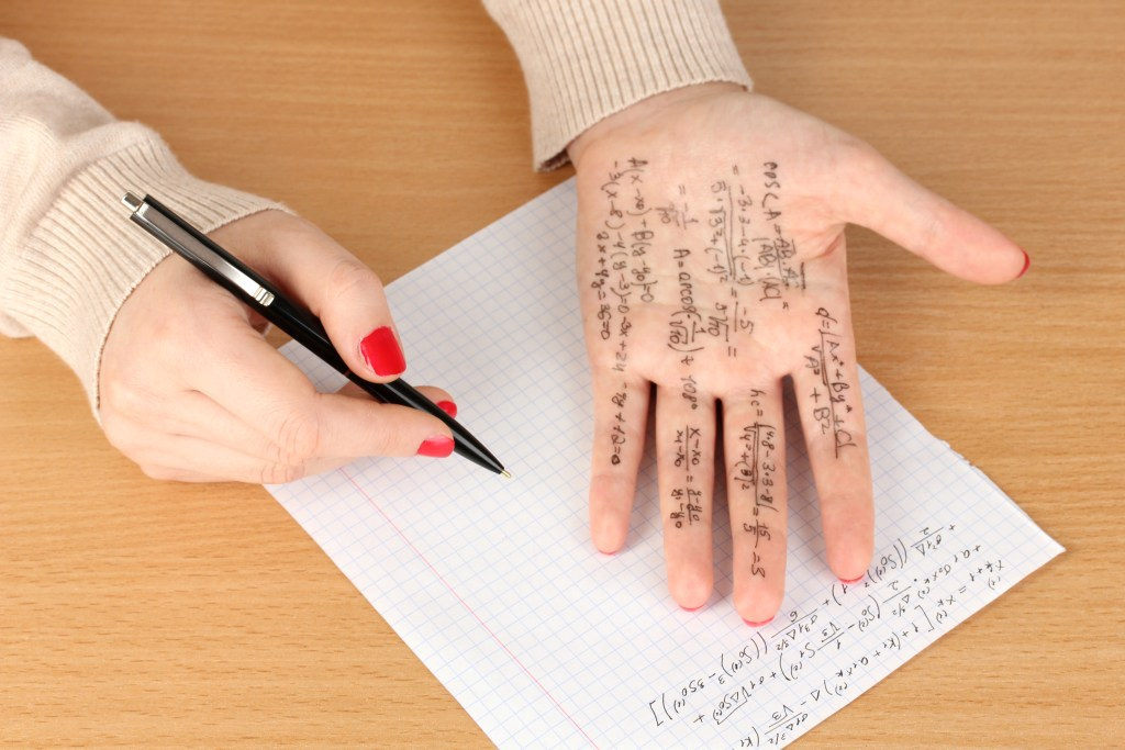 hand on table with cheat sheet
