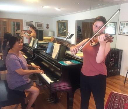 Mimi accompanying student on piano
