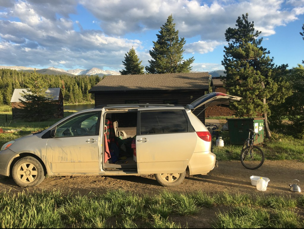 Minivan parked at camp location with a view of the Continental Divide