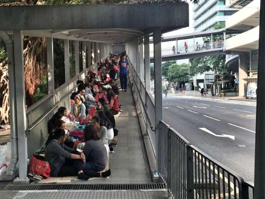Frauen sitzen auf Pappkartons auf einer Fußgängerbrücke