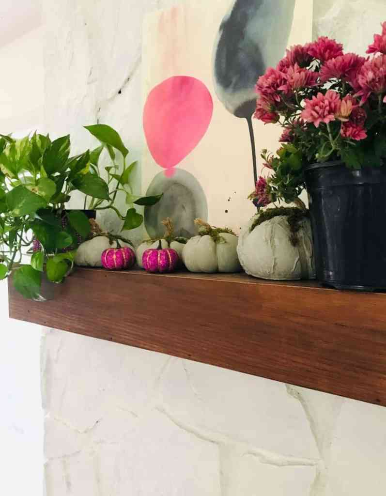 Bring it all together. Fireplace mantel with concrete and glitter pumpkins and fresh flowers. Pumpkin decorating ideas.