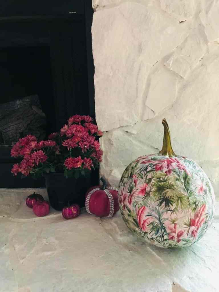 Decoupaged pumpkin on the fireplace arranged with fresh flowers.  Pumpkin decorating ideas.