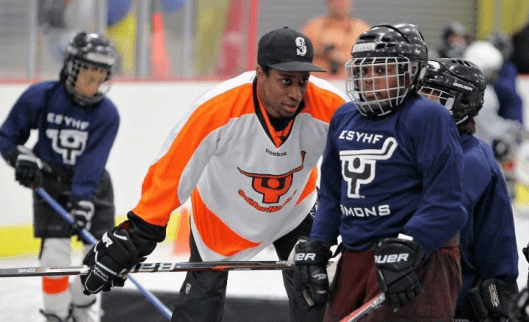 Flyers forward Wayne Simmonds gives tips to a Snider Hockey participant. The program's ice and educational activities helped sell Bronx leaders on the KNIC project.