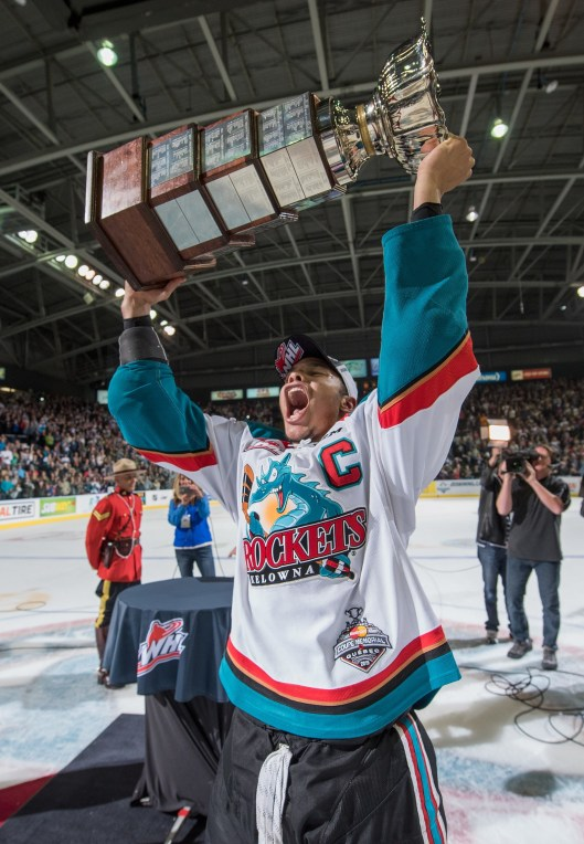 Madison Bowey hoists WHL championship trophy, perhaps a practice lift for the Memorial Cup  (Photo by Marissa Baecker/Kelowna Rockets).