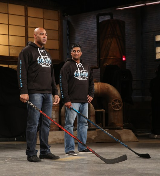 "Ex-NHL enforcer Donald Brashear, left, with partner Jibin Joseph show off Brash87 hockey sticks to the cast of CBC's ""Dragons' Den."""