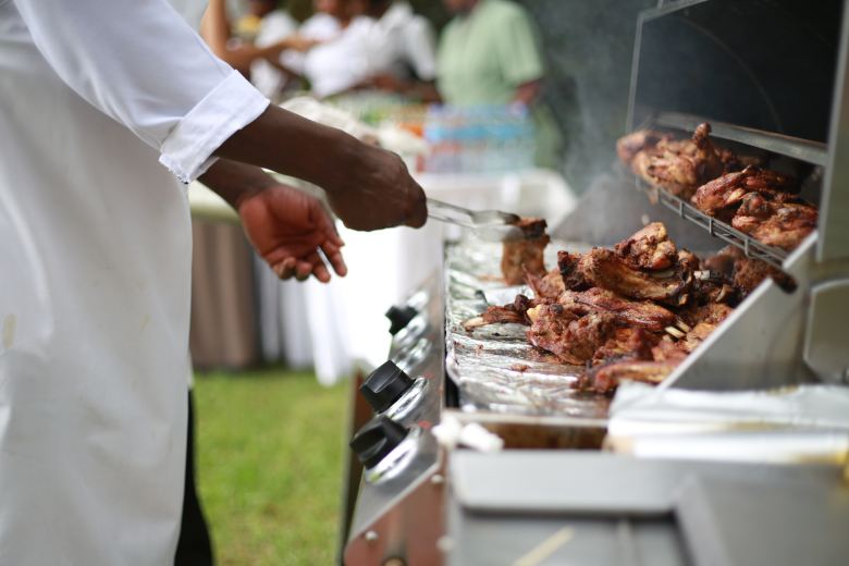 Image description: a black man flips grilled chicken on a stainless-steel grill on a summer day.