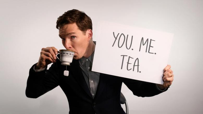 "Benedict Cumberbatch sipping tea from an ornate teacup and holding a sign that reads, ""You. Me. Tea."""