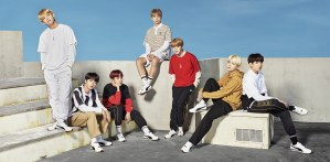 Members of BTS posed on white steps and partitions against a blue sky, wearing clothes from their line.