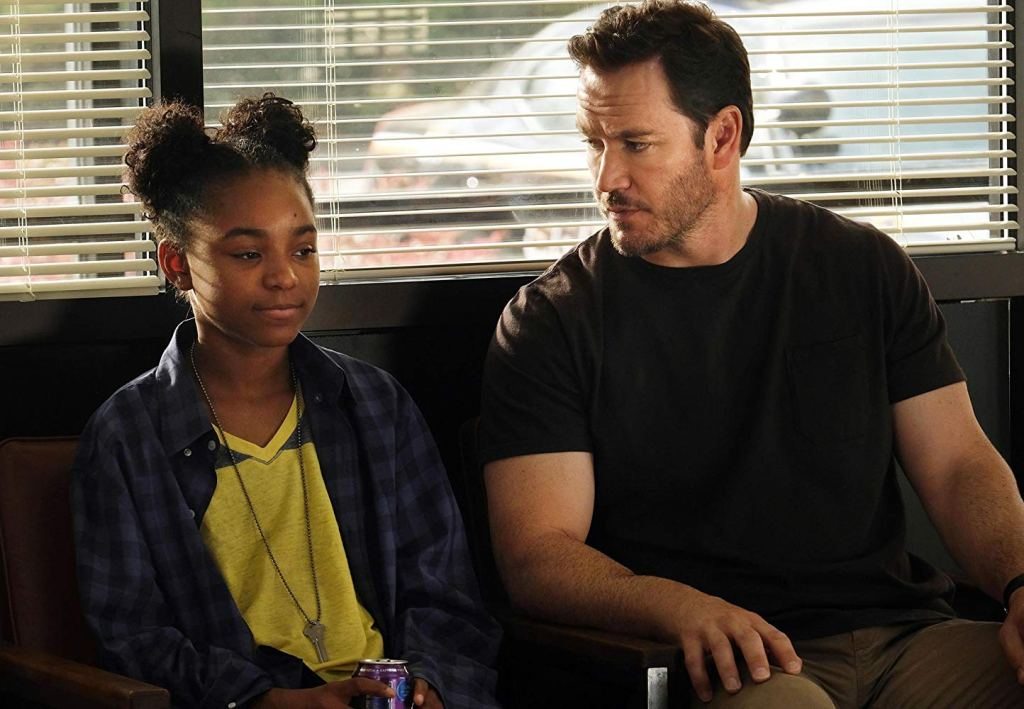 Saniyaa Sidney and Mark-Paul Gosselaar in The Passage. CR: Eliza Morse/FOX. Amy, in a blue plaid shirt and yellow and green T-shirt with her key on her necklace, sits next to Gosselaar, who wears a dark T-shirt and khaki pants. They are waiting in a police station.
