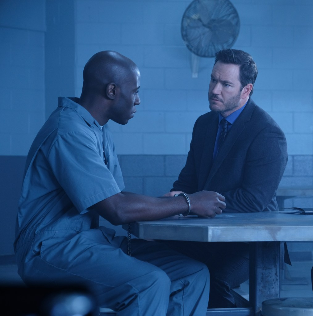 L-R: McKinley Belcher III as Anthony and Mark-Paul Gosselaar as Brad in The Passage.  CR: Eliza Morse / FOX. Anthony is in a grey prison jumpsuit and has handcuffs on his wrists. Brad is in a dark suit with blue dress shirt and dark blue tie.