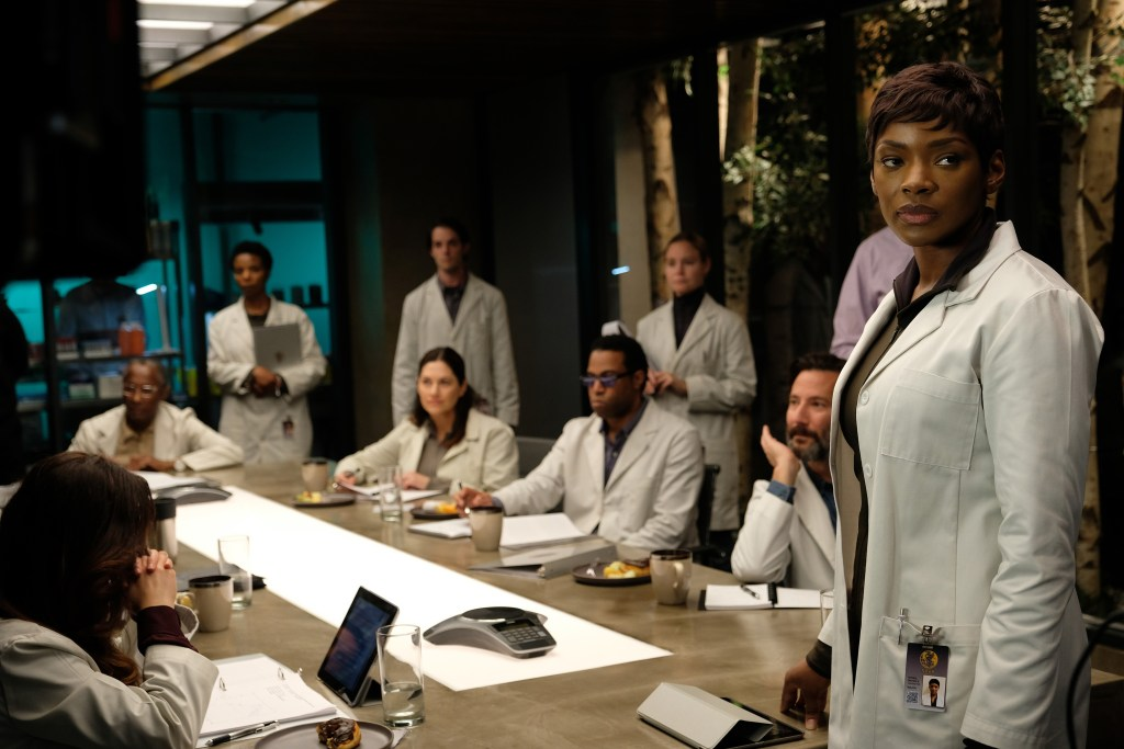 Caroline Chikezie as Dr. Sykes (R) in The Passage. CR: Eliza Morse / FOX. Dr. Sykes, in her white lab coat, stands at the head of a conference table where her scientific crew are meeting.