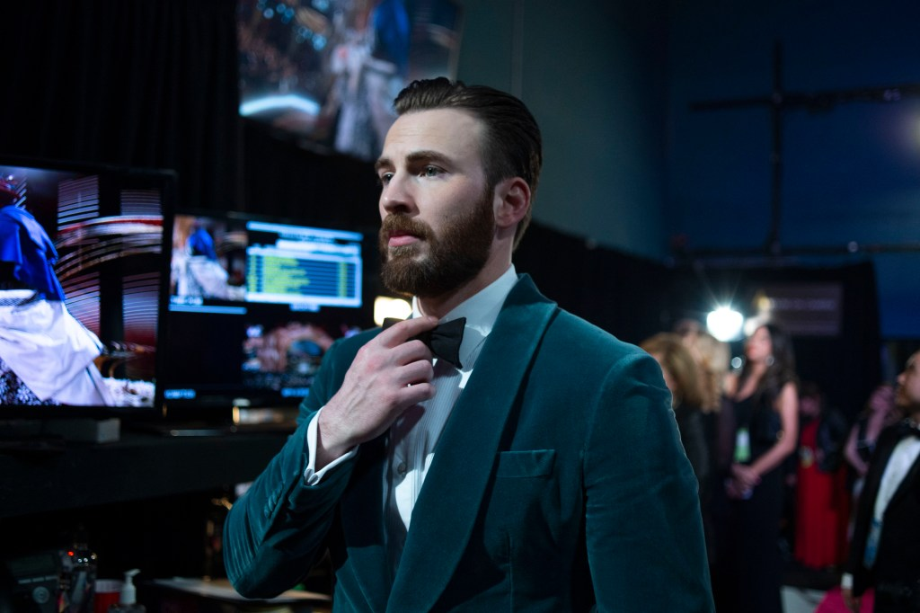 In a green velvet tux jacket, Chris Evans straightens his black bow tie as he prepares to introduce one of the categories for the Oscars.