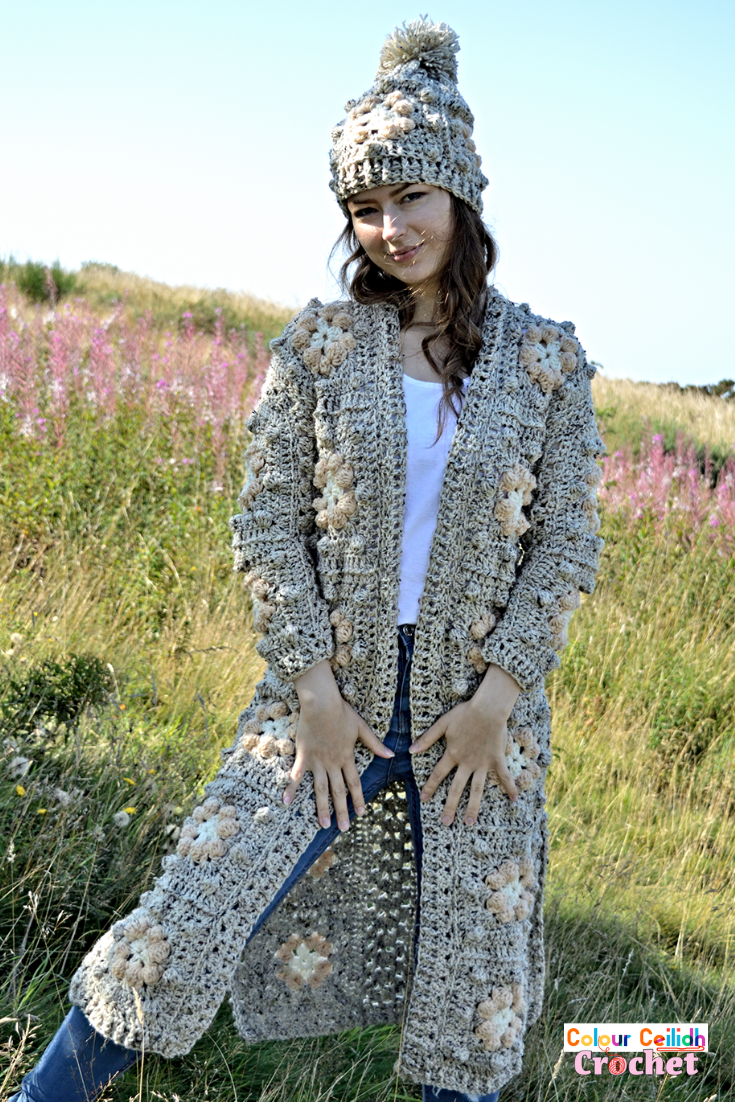 This crochet Bobble Flower granny square cardigan is a long sweater coat made with a matching ribbed bobble hat. This pattern provides bobbles of comfort, squishiness and you just want to live in it and wrap yourself in it! Made in monochromatic color scheme, this easy granny square cardigan comes in 9 sizes, includes a layout diagram and a YouTube tutorial as well.
