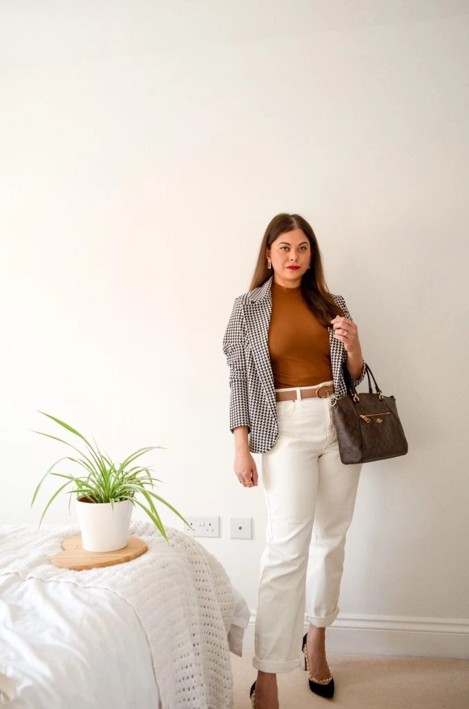 French style white jeans outfit with brown halter top with houndstooth blazer and designer belt and coach bag.