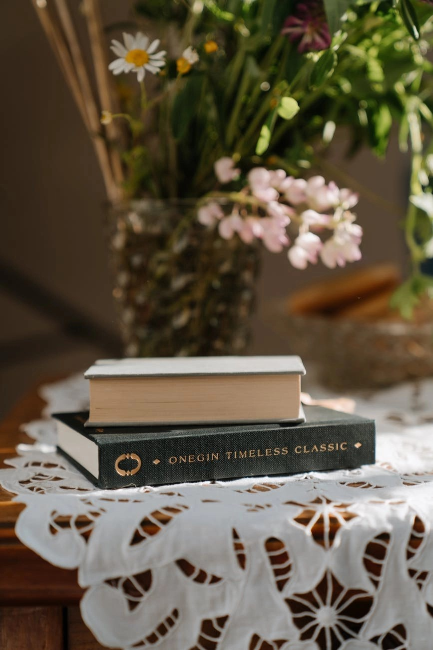 black and white book on white and brown floral table cloth
