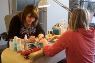 Nail technician, Pam Pickinpaugh, giving Cailin Silsox a manicure.
