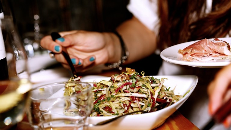 Person with teal nail polish holds dish of prosciutto and serves themselves salad at restaurant