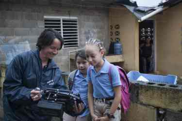 Dominican girls watching themselves on the field monitor as they are being filmed. Manabao, Dominican Republic.