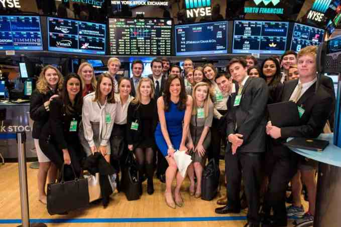 "During a visit to the New York Stock Exchange, students met with Kelly Evans '07 (in blue dress), co-anchor of ""Closing Bell"" on the CNBC business news channel."