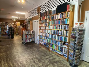 Inside a book store with shelves of books and employee working