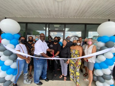 Group of people standing outside business named Special Blends Bartending School ready to cut the ribbon for a ribbon cutting ceremony