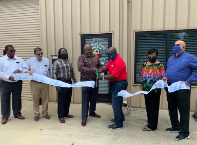 Group of people standing outside The Good Lord's Mobile Welding Service shop and cutting the ribbon at the ribbon cutting ceremony
