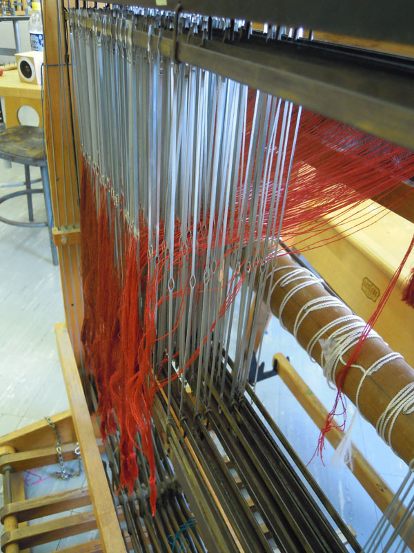 Here are warp threads pulled through the eyes of heddles on their corresponding harnesses.
