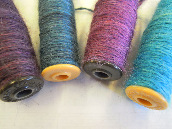 Bobbins wound with hand dyed alpaca weft.
