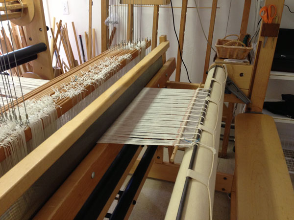 One method of how to attach the warp to the front beam. Another method would be to lay the warp threads directly on the sandpaper beam to limit the amount of waste used to tie on.