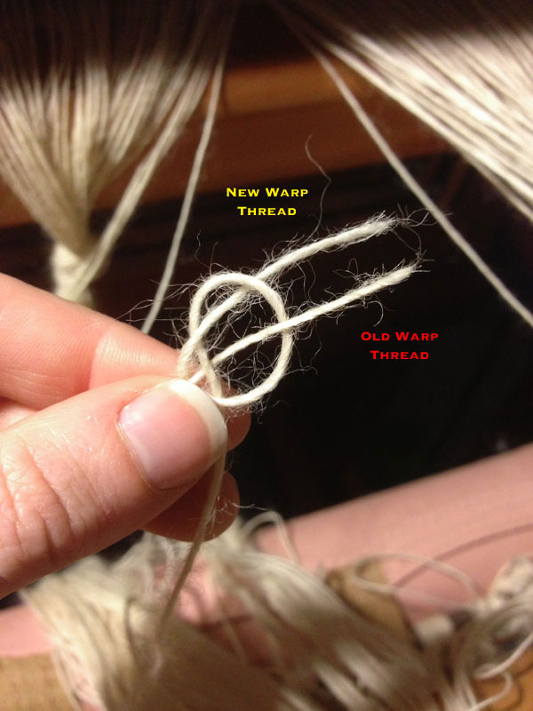 I slide the loop I've created over the tip of my thumb and pull the old warp thread through the loop.
