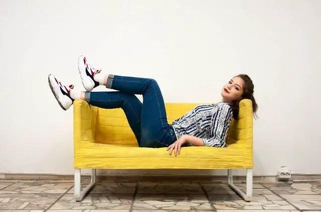 girl laying on a yellow sofa