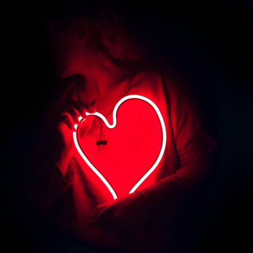 Woman holding a heart-shaped neon sign