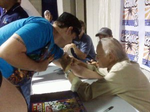 Stan Lee Signing a Man's arm at a comic convention.