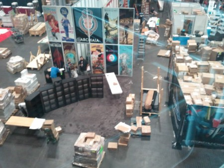 """The Archaia/Boom booth, at Noon Wednesday. To the right, the """"storeroom"""" for a videogame company takes up half of their booth."""
