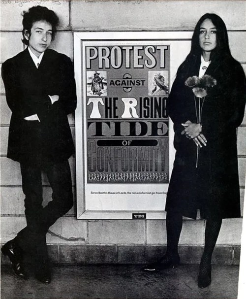 Bob Dylan and Joan Baez flanking a Seymour Chwast poster, 1964. Photo: Courtesy SVA Picture Collection.