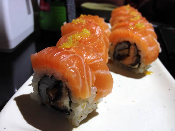 Skin Sushic: Uramaki de pele de salmão grelhada, com uma fatia de salmão em volta, raspas de limão e molho de maracujá.