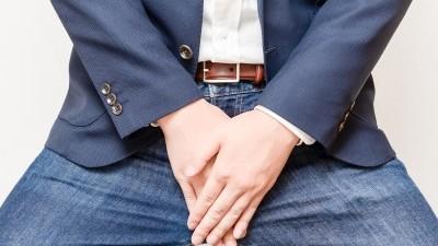股間を抑える男性