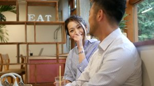 A man and a woman sitting by the window of a cafe, talking.