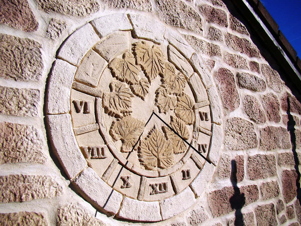 dessin sur crépis de façade personnalisation de facade avec cadran solaire rond et feuille de vigne sur facade fausses pierres