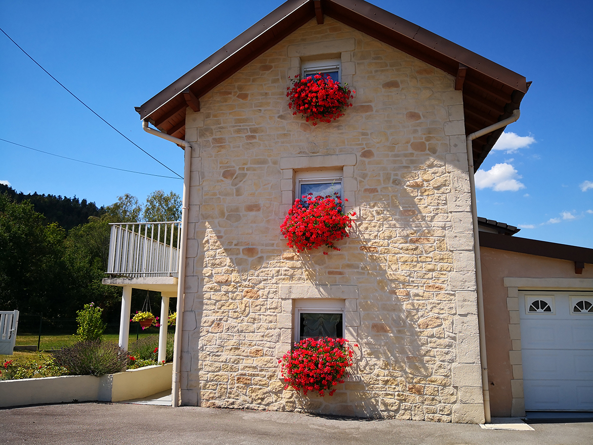 enduit traditionnel à la chaux aérienne sur façade de maison en pierre dans les vosges 88