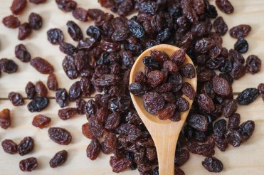 Raisins in a wooden spoon, close-up