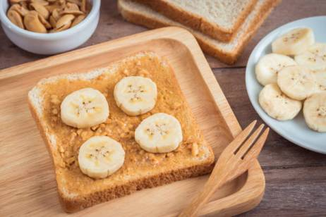 Bread with peanut butter and banana on plate