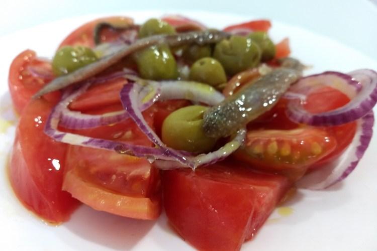 Ensalada de tomate con cebolla, anchoas y aceitunas partidas 1