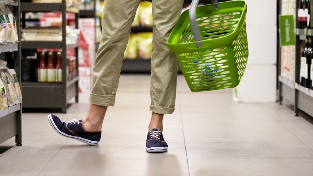Cropped image of a young man's legs and grocery basket