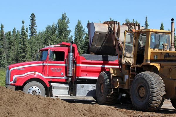 Dump truck being loaded by front end loader