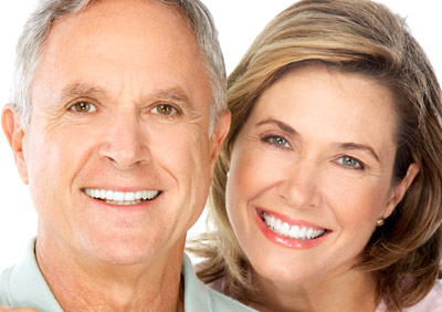 A middle-aged man and woman smiling with good teeth