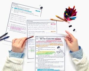 Woman holding color coded 2nd and 3rd grade reading passages