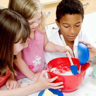 three children are mixing ingredients to learn math while cooking in school